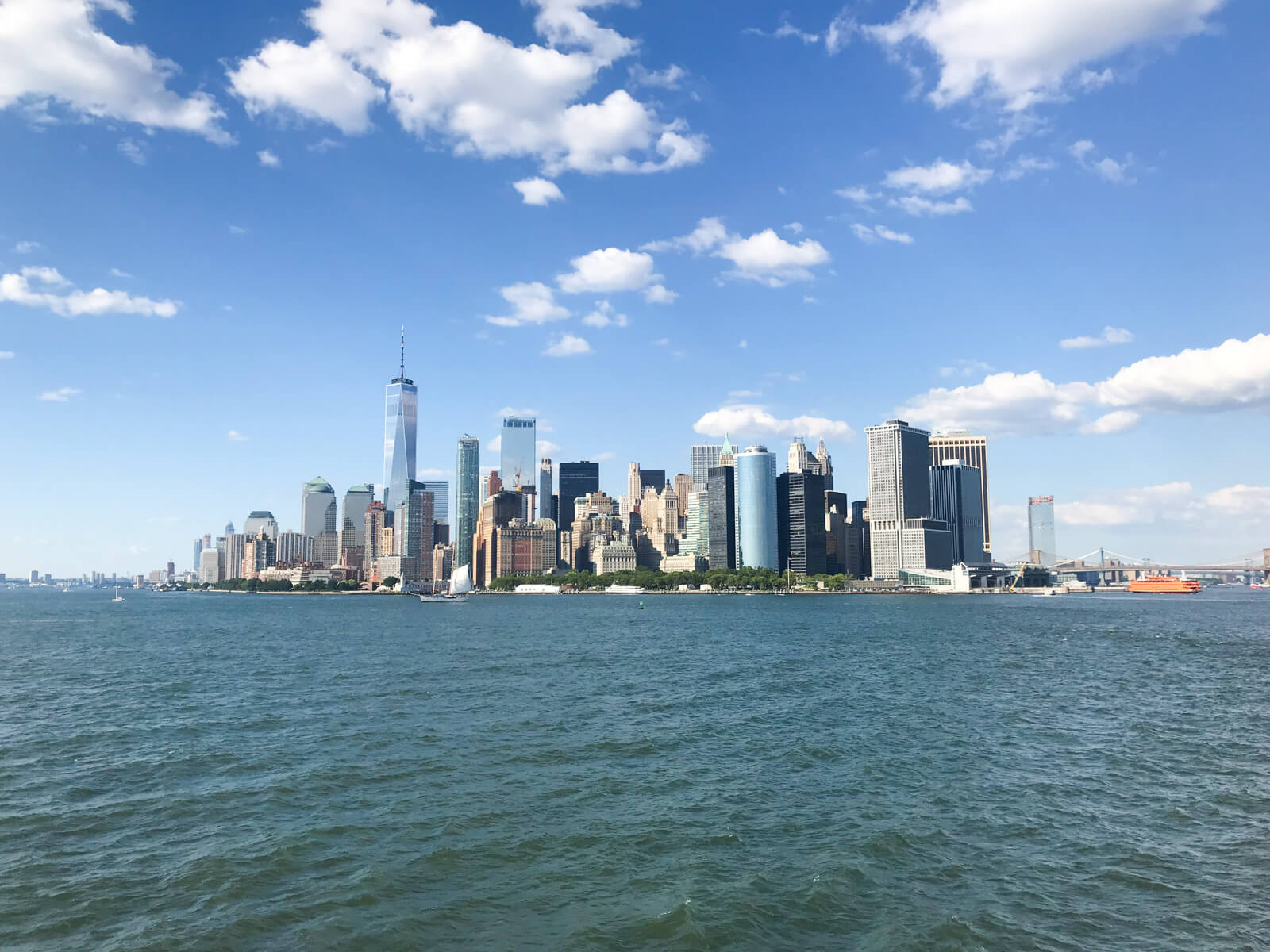 A view of the New York City skyline with the ocean in the foreground. The sky is blue with several clouds