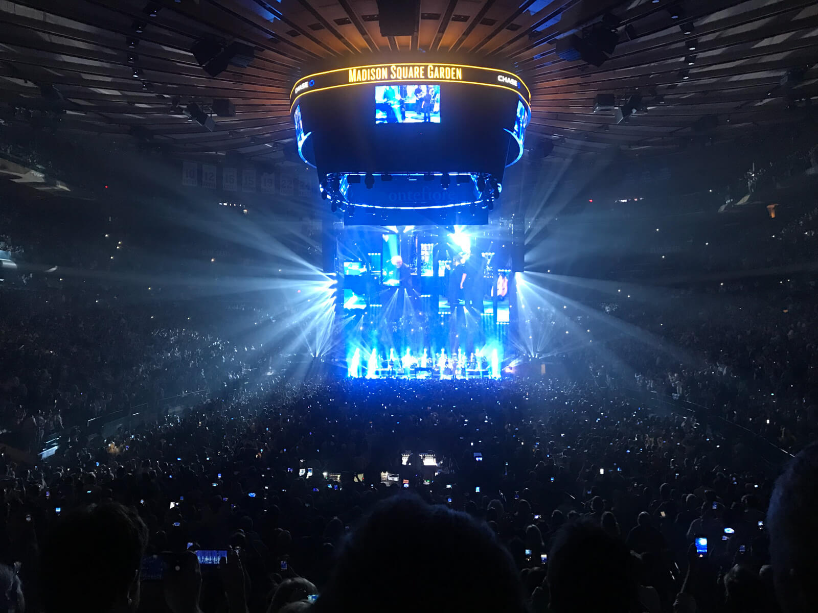 "The inside of a concert venue. The stage has a lot of blue lighting and a fixture above the stage and on the ceiling of the venue reads ""Madison Square Garden"" and has screens with close views of what is happening on stage"