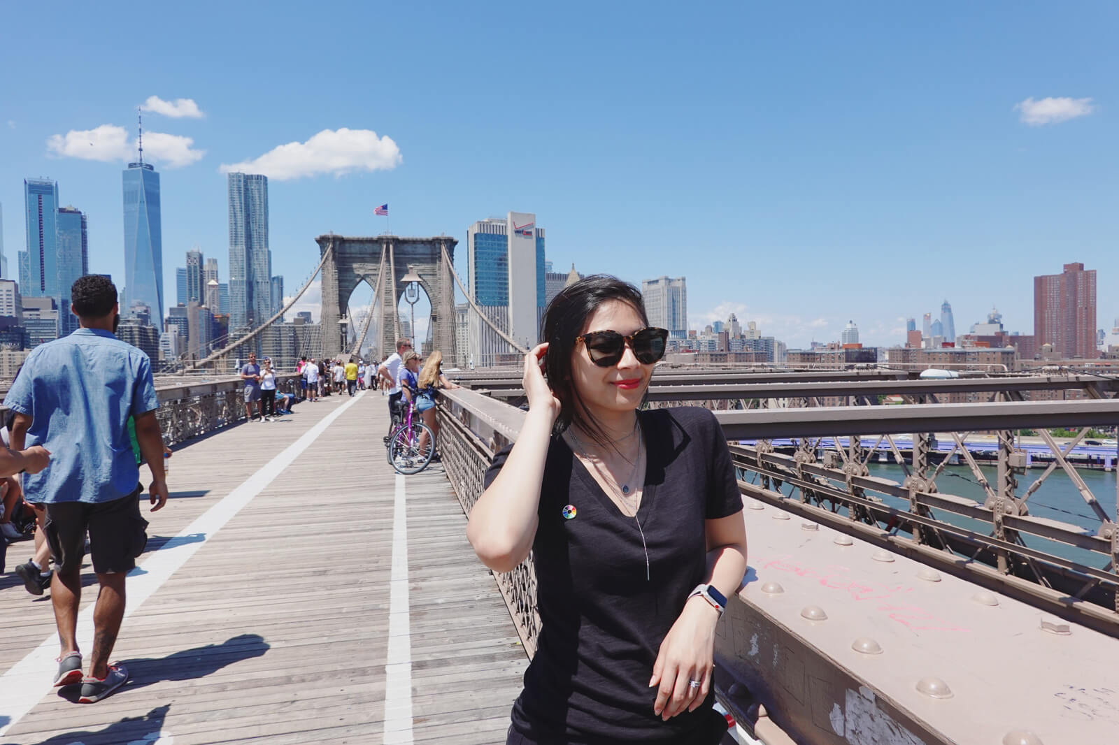 A woman in a black t-shirt, wearing sunglasses. She is standing on a bridge with high-rise buildings in the background. There are other people bicycling and standing on the bridge