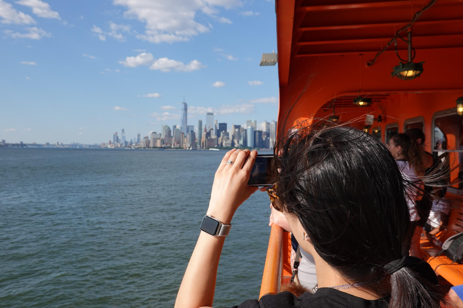 The back of a woman's head as she takes a photo with her smartphone from a ferry. In the distance is a city with high-rise buildings