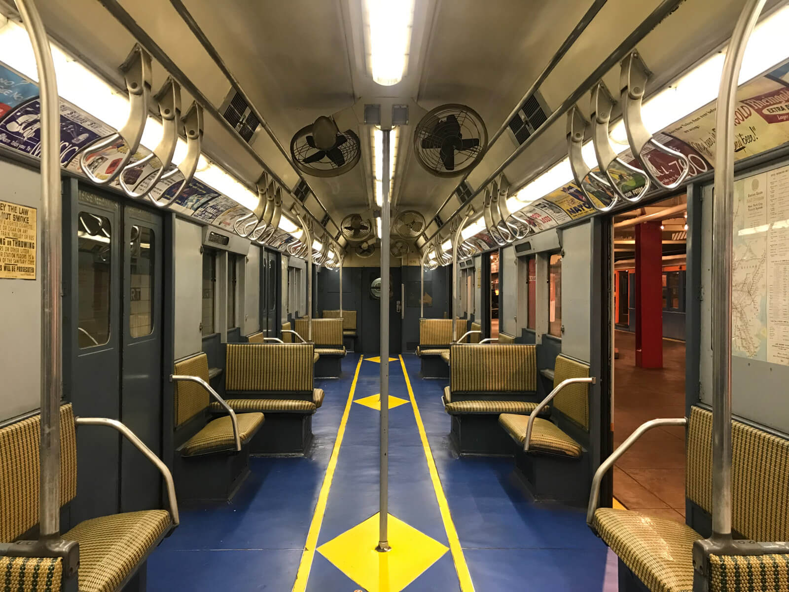 The inside of a different train carriage with a blue and yellow floor