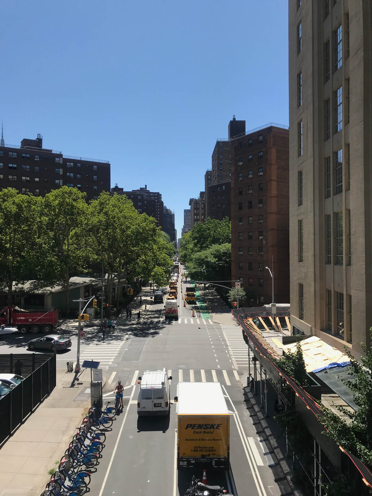 A daytime, high-angle view of a street in New York on a sunny day. Many bicycles are parked on the side of the street and there are a couple of vans and small trucks driving on the street