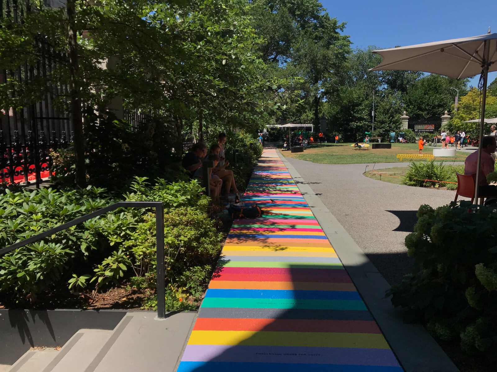 The inside of a park with a horizontally-striped short path in different colours. Some trees provide shade on the path