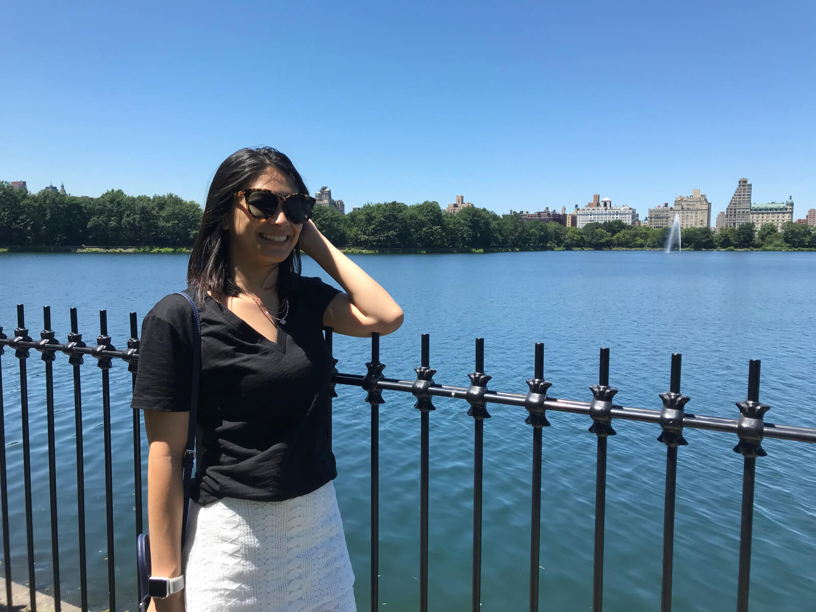 A woman wearing sunglasses, a black t-shirt and white skirt, standing by a black fence. In the background is a large lake and buildings and trees further into the distance