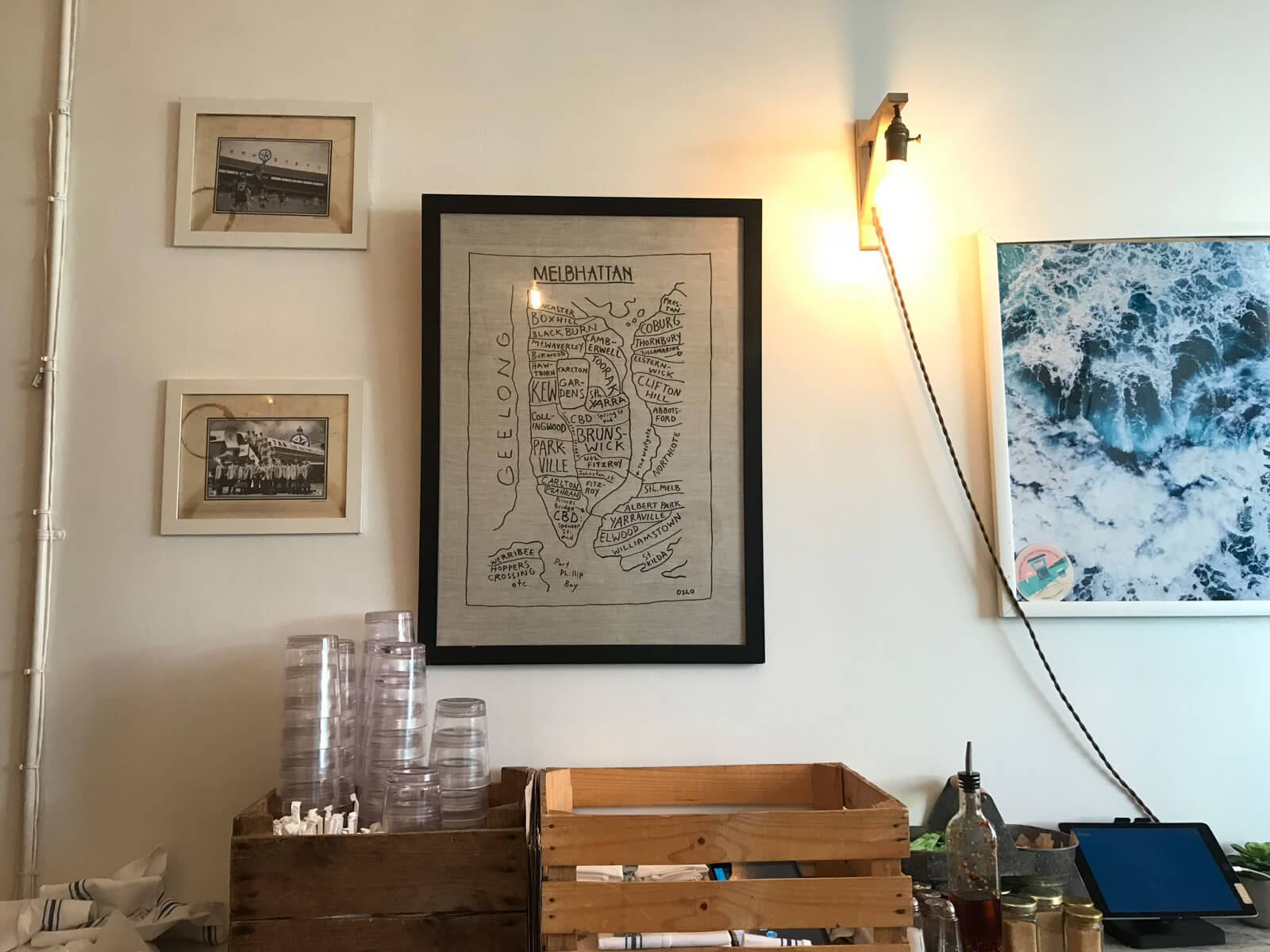 "The interior decor of a cafe, with black-and-white photographs on the wall and a piece of drawn artwork titled ""Melbhattan"", with outlines and labels resembling a map of a fictitious area"