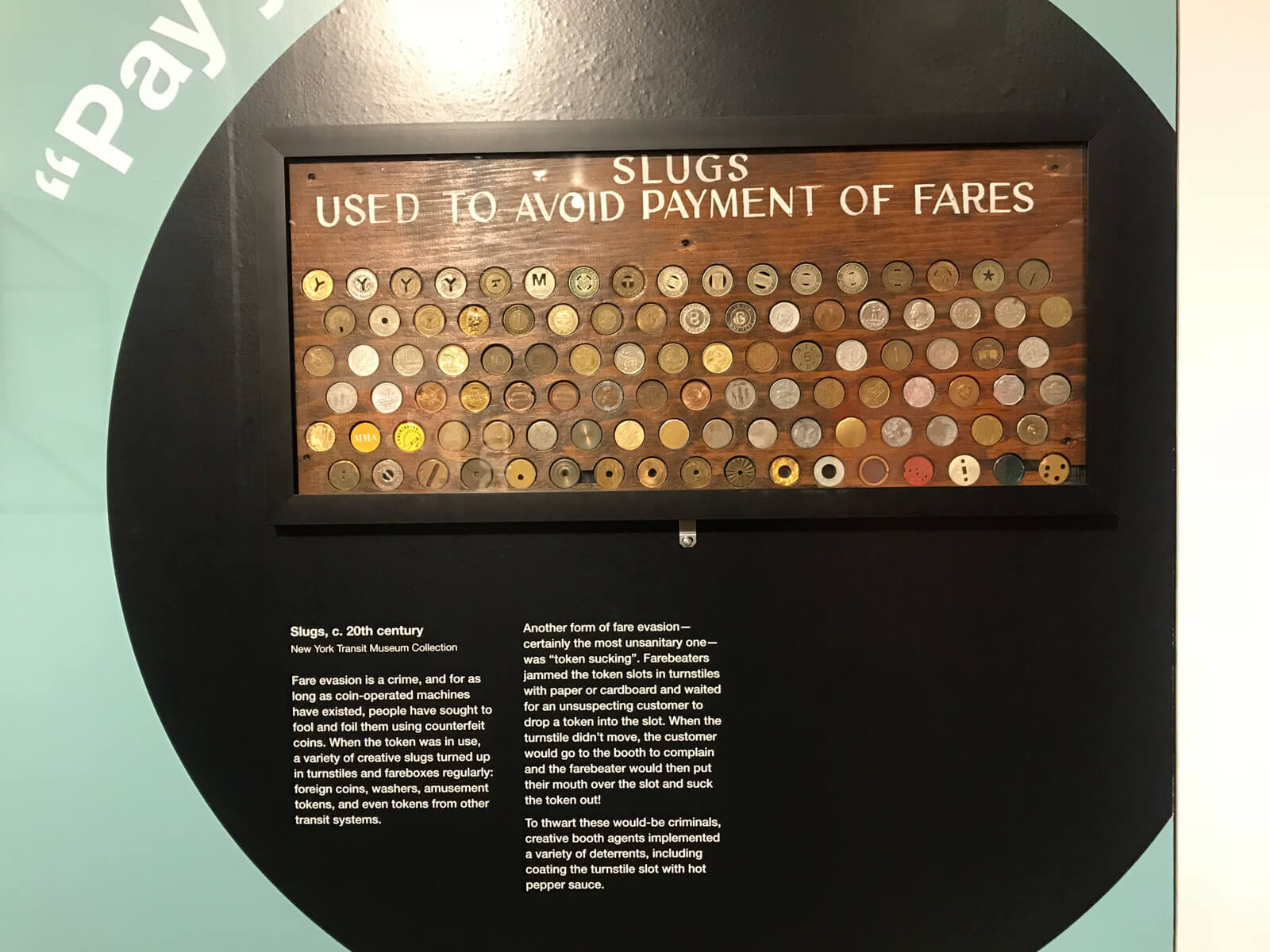 A display on a wall of many different fake tokens, resembling metal coins, used to avoid paying fares to ride the train