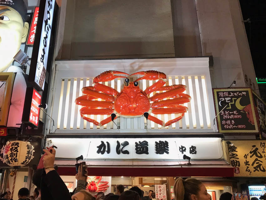 A moving crab sculpture above a store
