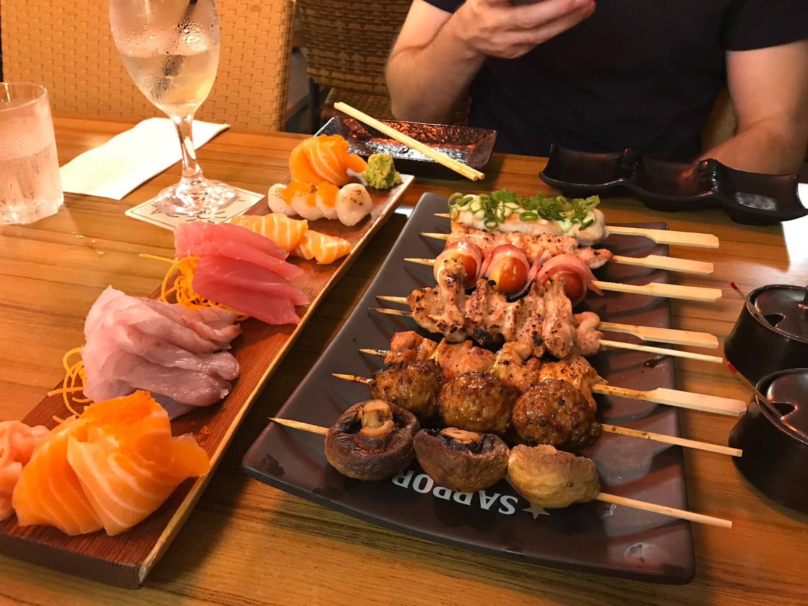 A restaurant table with a plate of small skewers of meat, and sliced raw fish on a separate plate