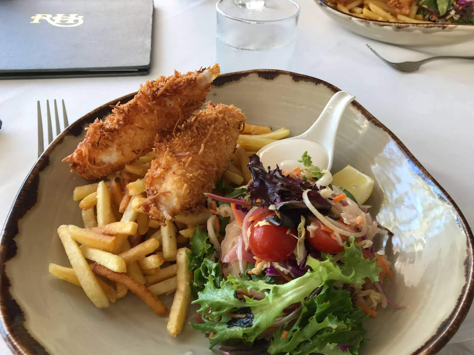An irregular shaped bowl with some fries, garden salad and battered fish.