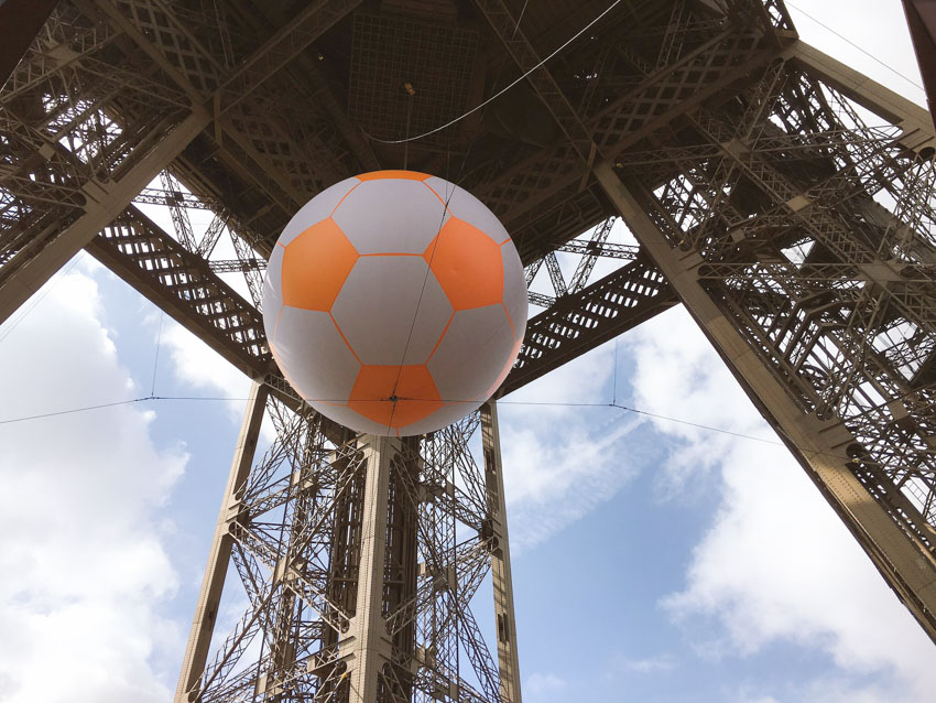A big inflatable football hanging from the centre of the Eiffel Tower for Euro2016