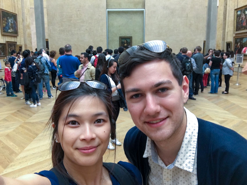 Myself and Nick distanced from a crowd looking at the famous Mona Lisa painting in the background