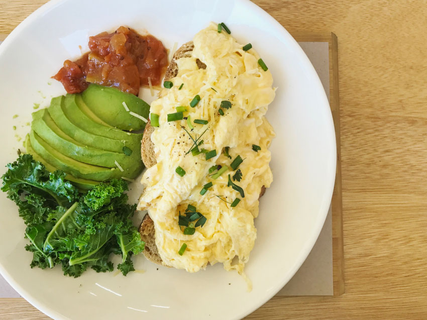Parmesan scrambled eggs with kale, avocado and tomato relish