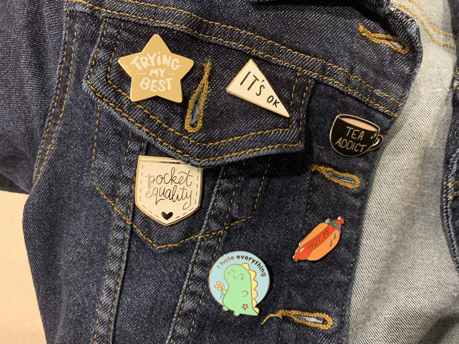 Part of a dark denim jacket accessorised with enamel pins