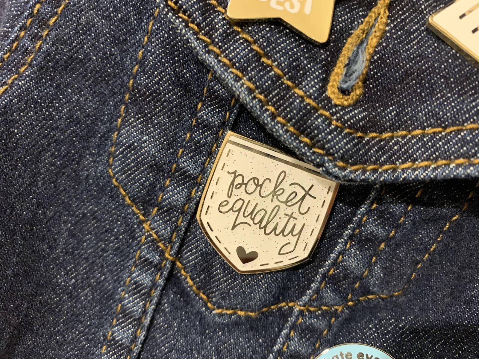 "A white enamel pin shaped like a pocket, reading ""pocket equality�, pinned on the pocket of a denim jacket"
