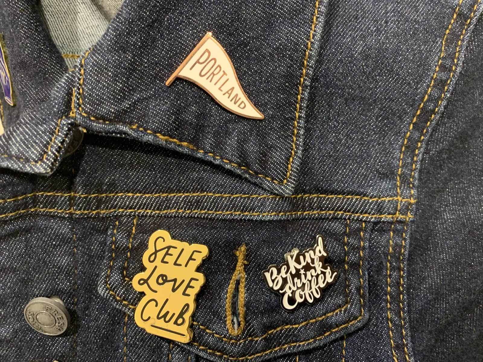 "A dark denim jacket with pins reading ""Portland�, ""Self-love club� and ""Be kind, drink coffee�."