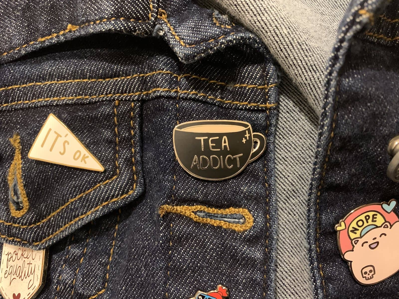 "A black enamel pin of a round bottom teacup with the writing ""Tea Addict� on it; it's pinned on dark denim"