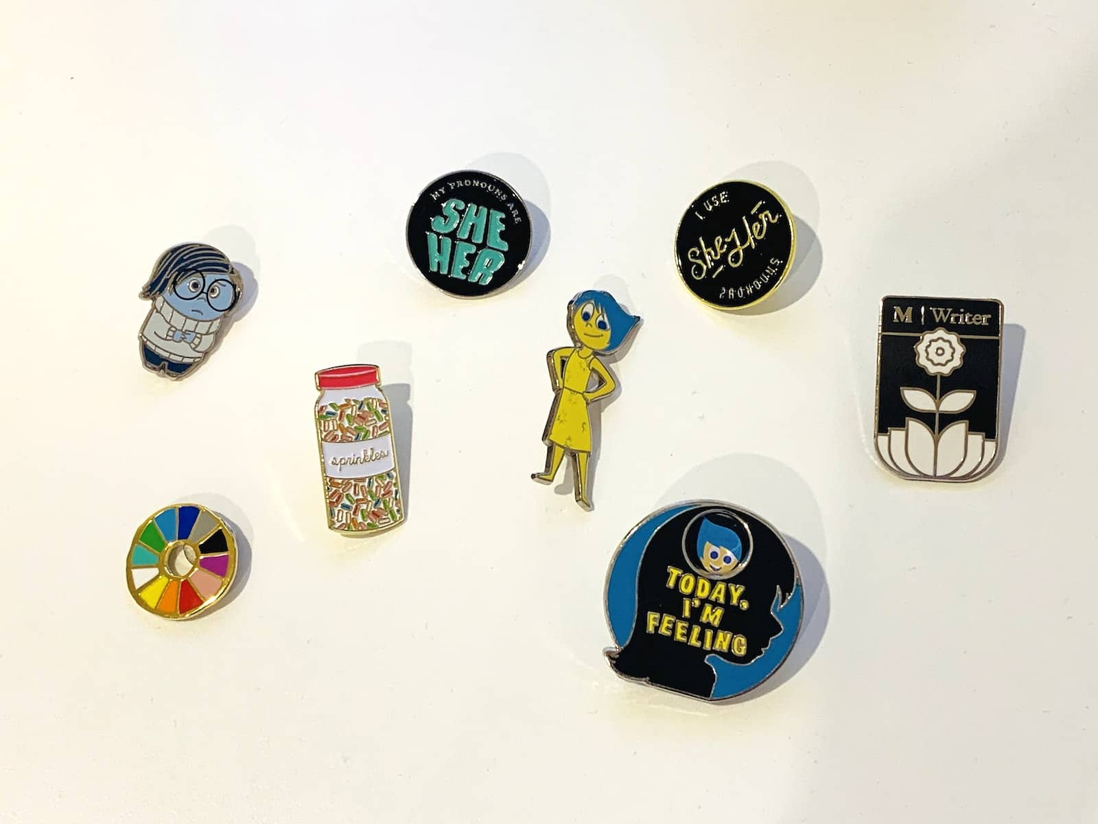 A handful of enamel pins on a flat white surface.