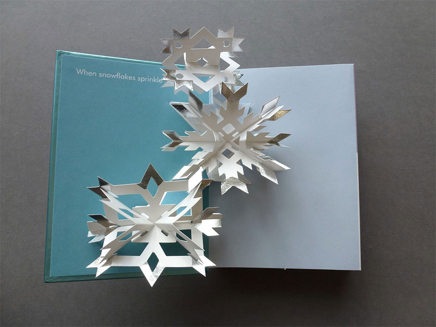 A pop-up book open to a page with a snowflake