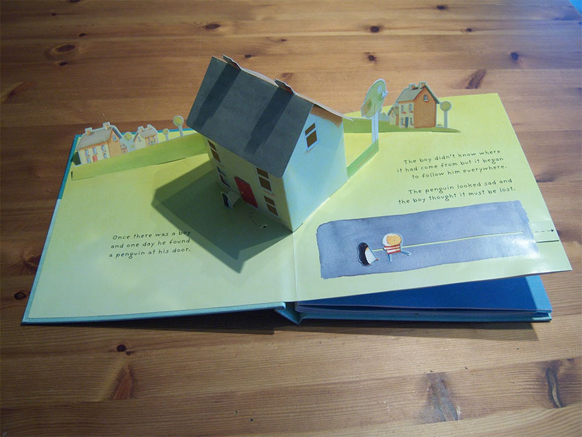 A pop-up book open to a page with a pop-up house in the middle
