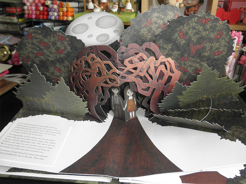 A cute pop-up book open to a page with a vertically-standing tree