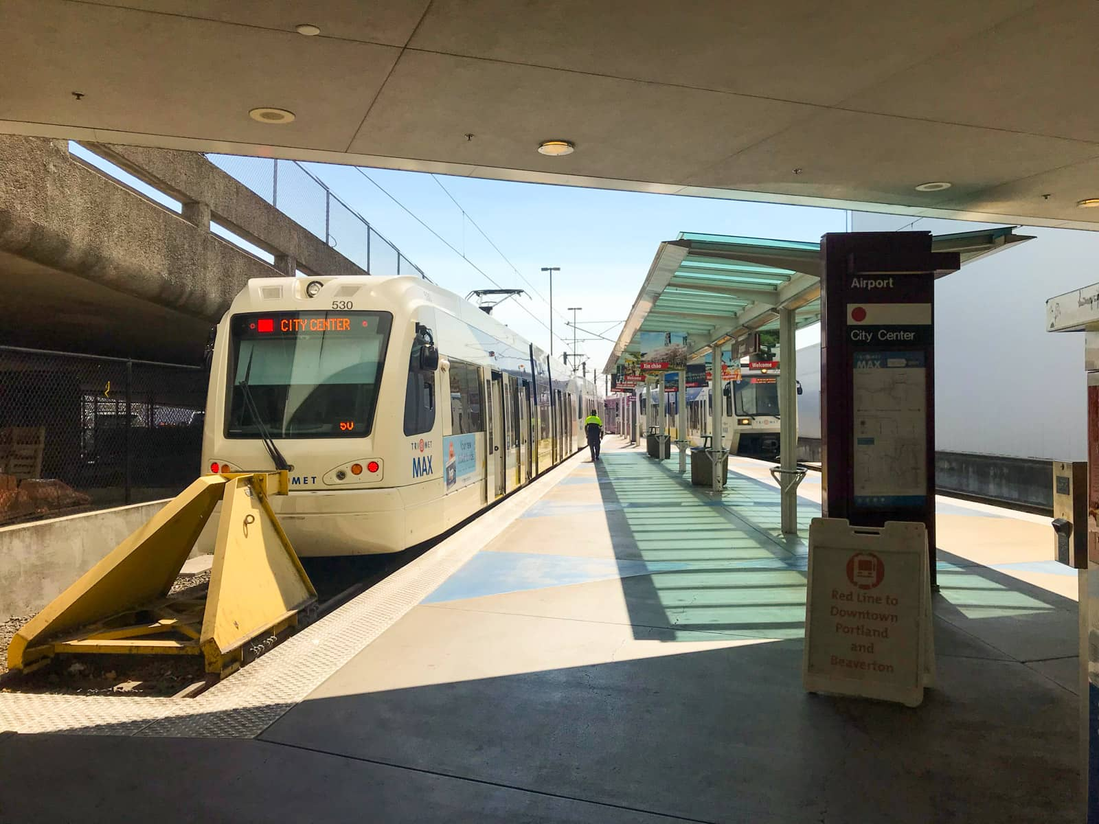 A light rail station at the end of the line. The foreground has adequate shade, and there is a light rail vehicle awaiting passengers.