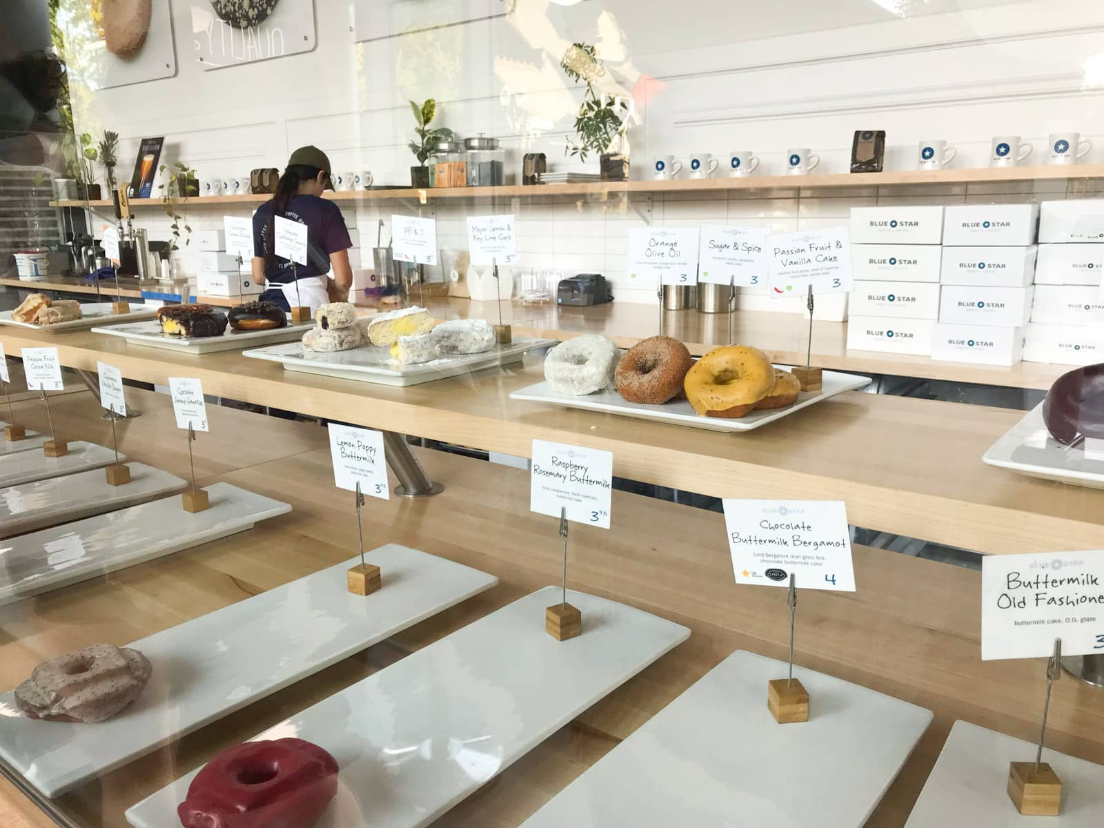The inside of a doughnut shop, with many gourmet doughnuts on display on long white trays.