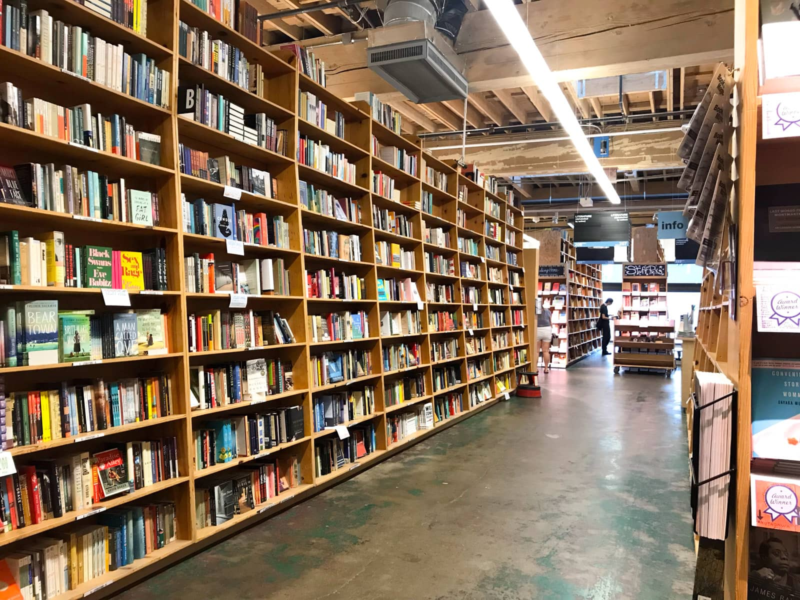 The aisle of a large bookstore, with wooden shelves as tall the ceiling. All the shelves are full of books