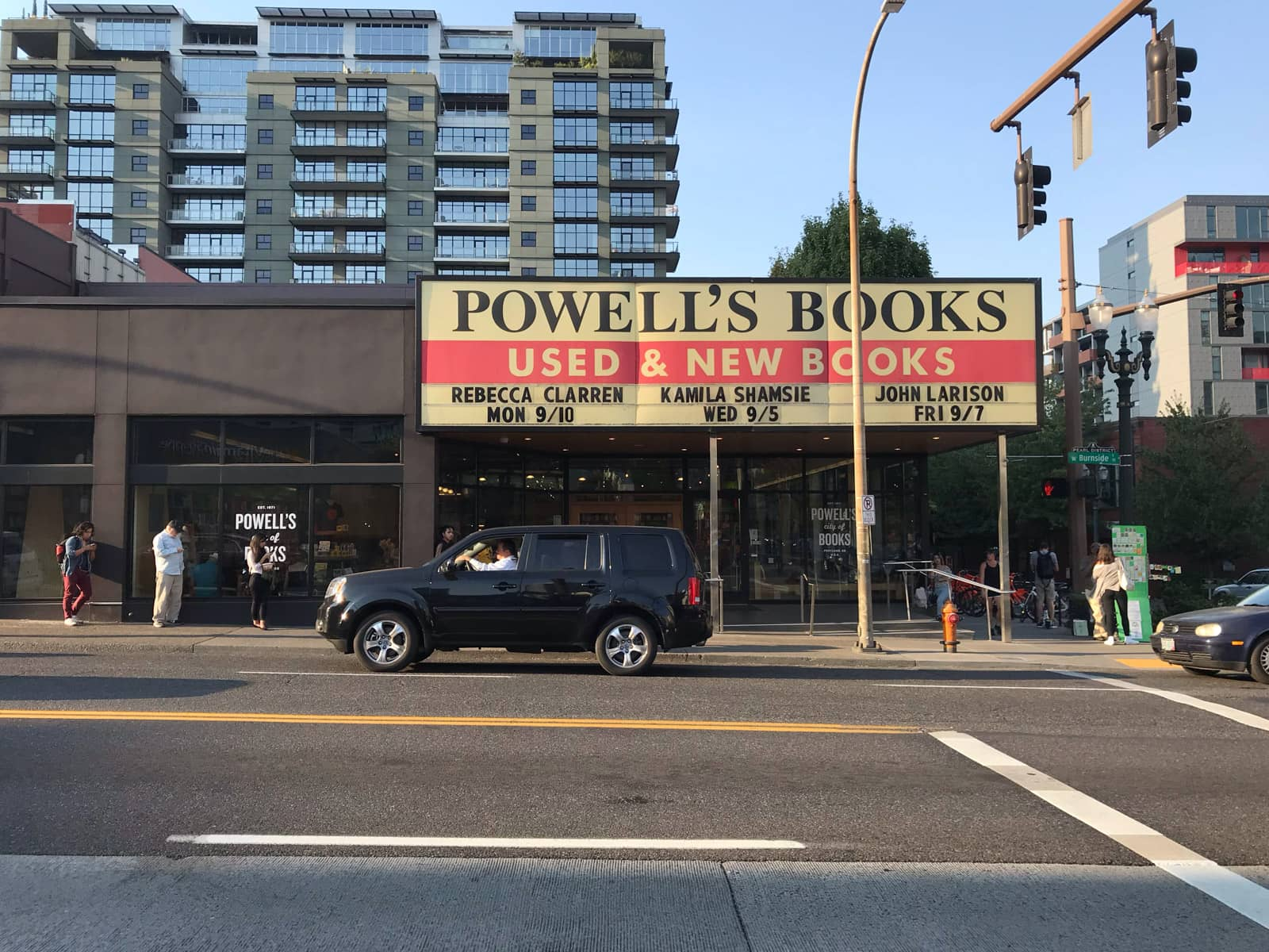"The front of a bookstore seen from the opposite side of a street. The signage reads ""Powell's Books – Used & new books"". A couple of cars can be seen driving past. There are a few people waiting in front of the bookstore."
