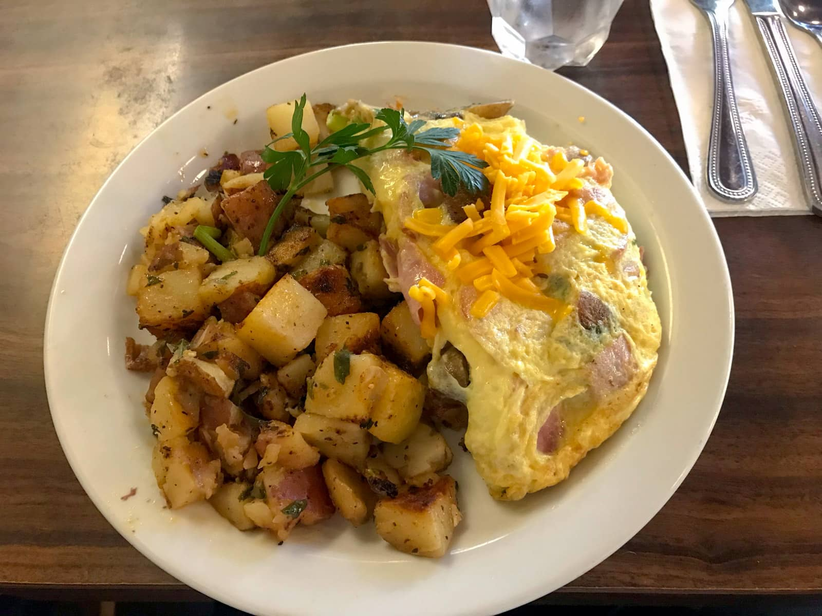An omlette with ham, served alongside roast potatoes and topped with American cheese.