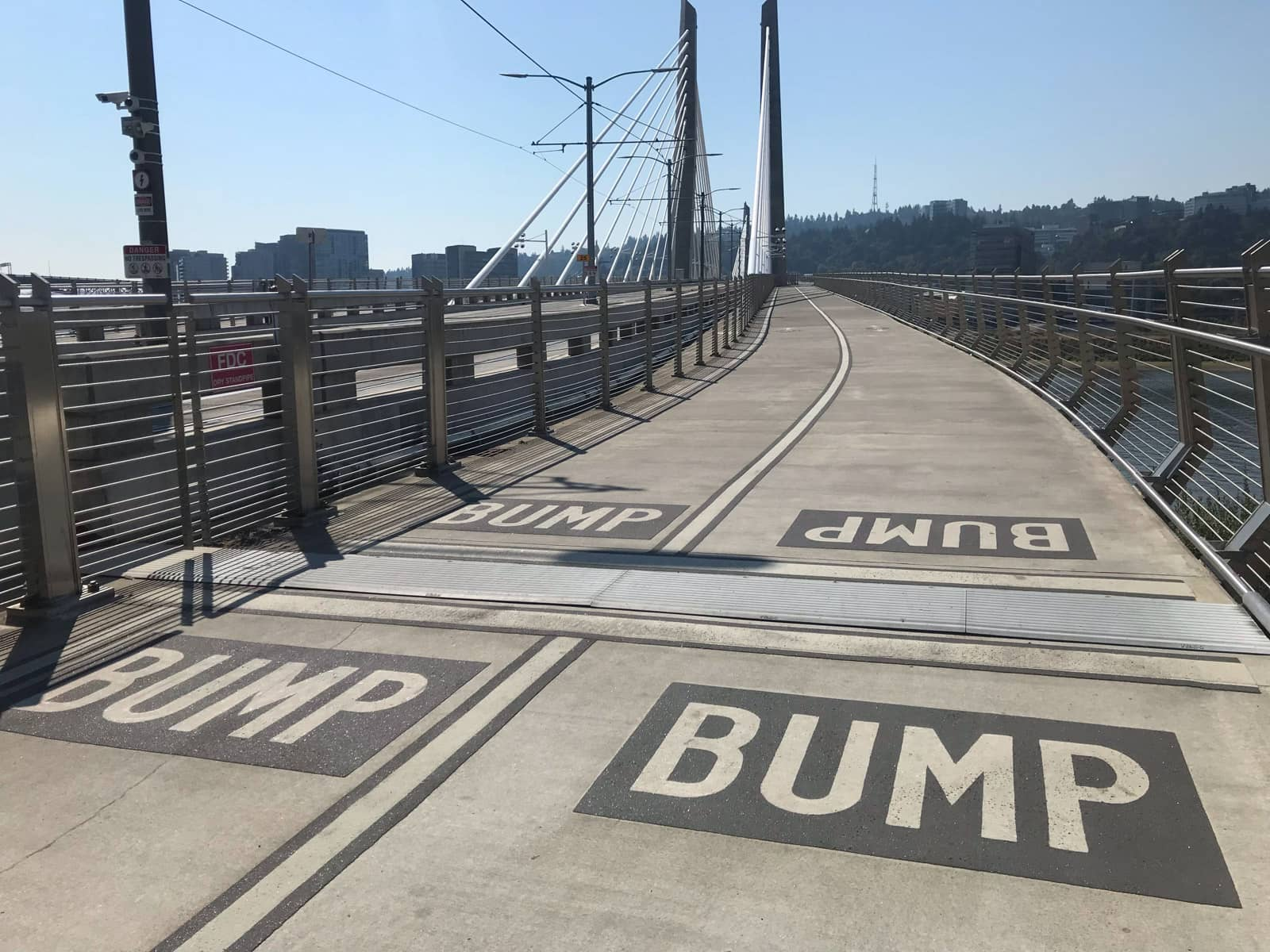 "The wide walkable path on a bridge with metal railings. Markings on the floor of the bridge read ""Bump"" to indicate a small bump in the path for pedestrians"