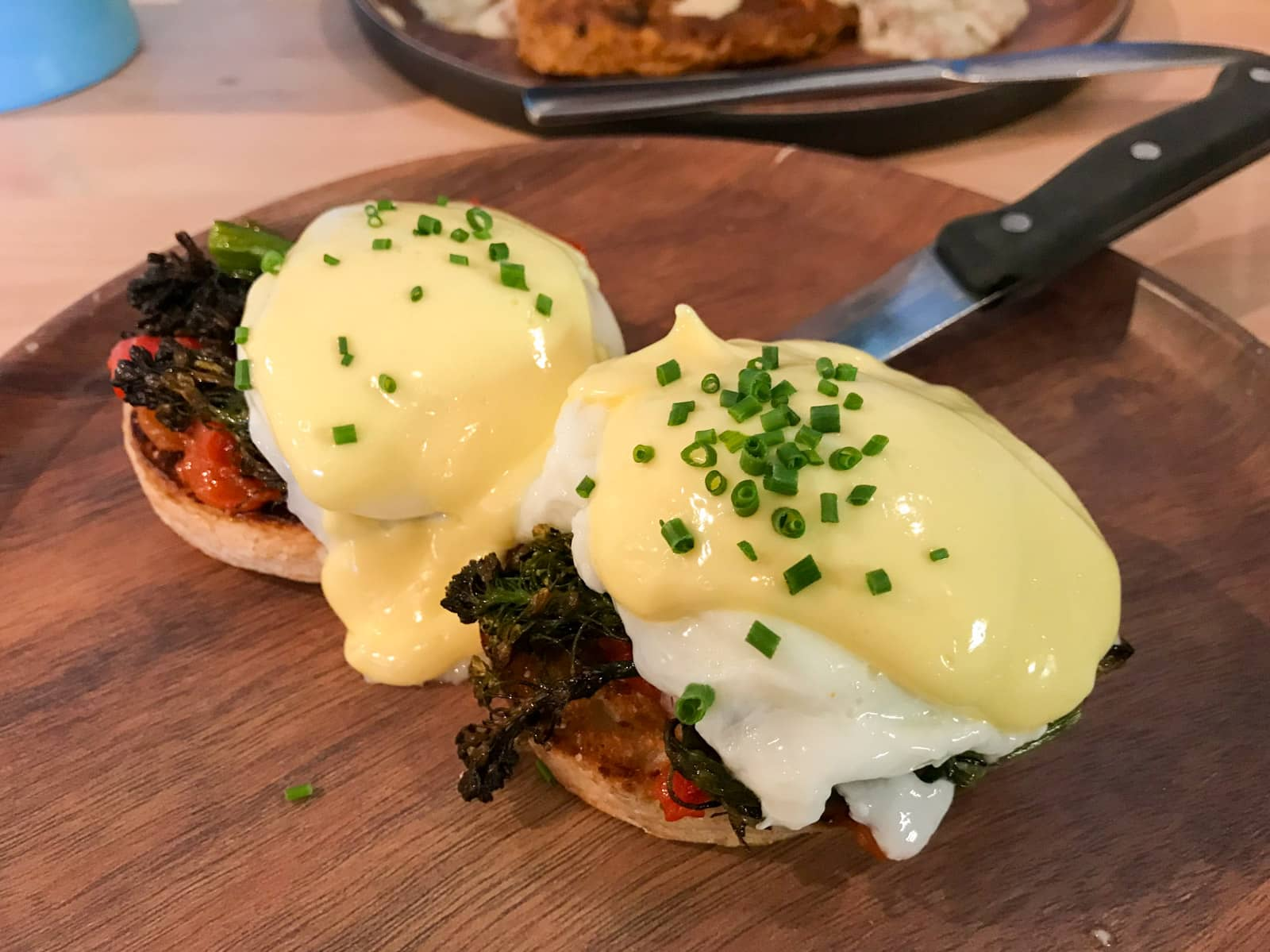 Poached eggs and hollandaise sauce served on buns with charred greens and tomato