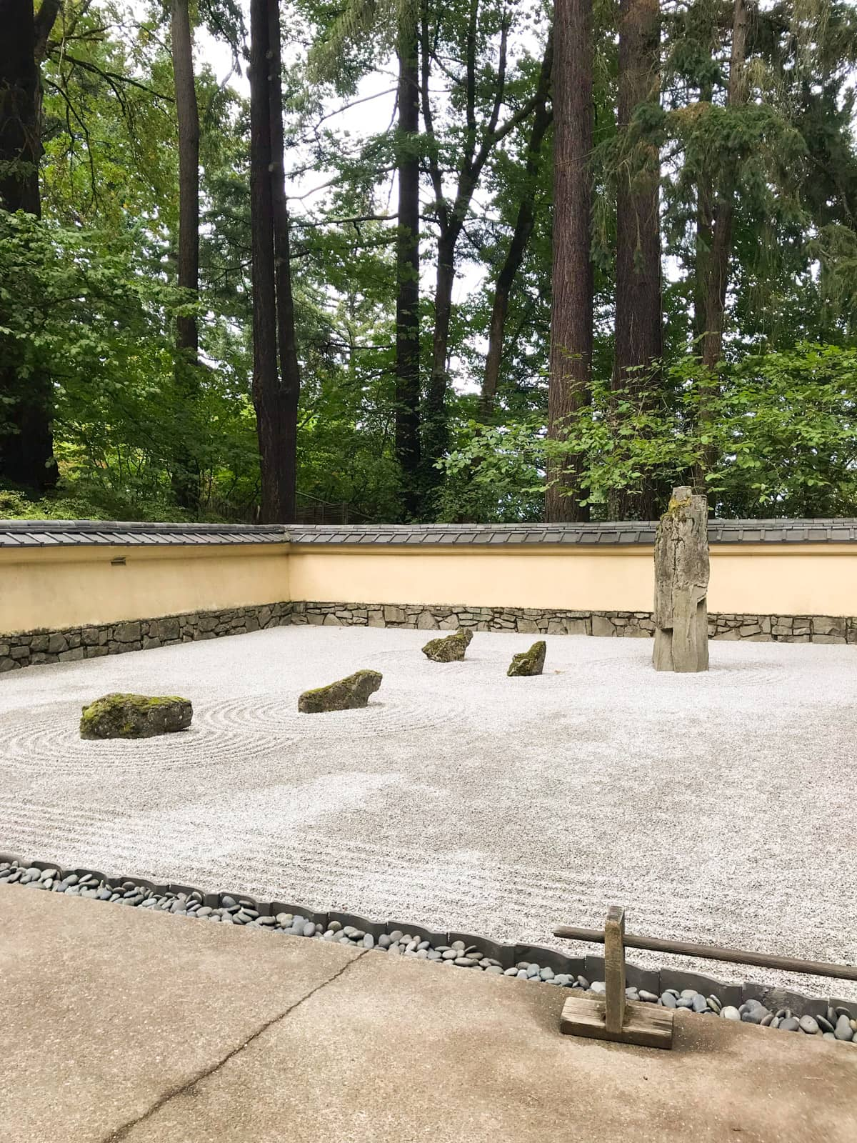 A Japanese zen garden covered with pebbles. Some rocks feature on the pebbles, in a neat formation