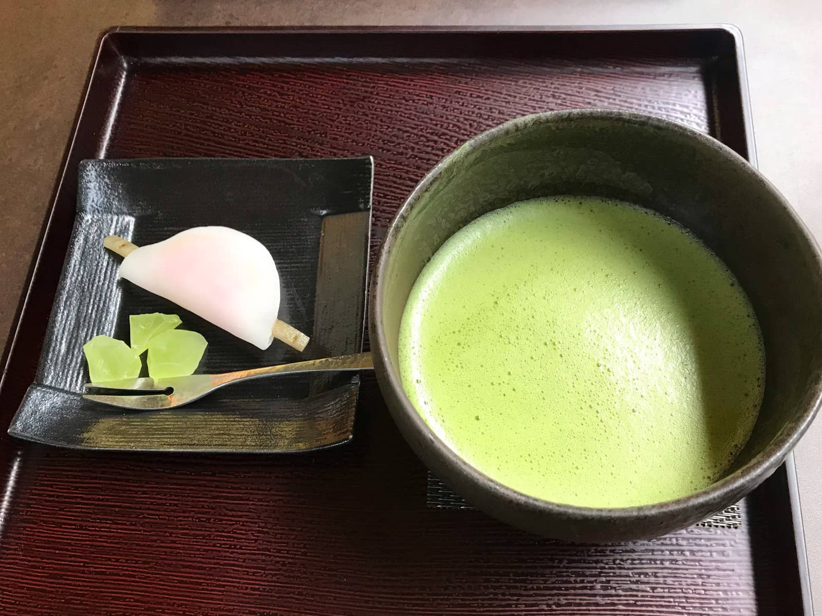A tray served with green tea matcha and some sweets