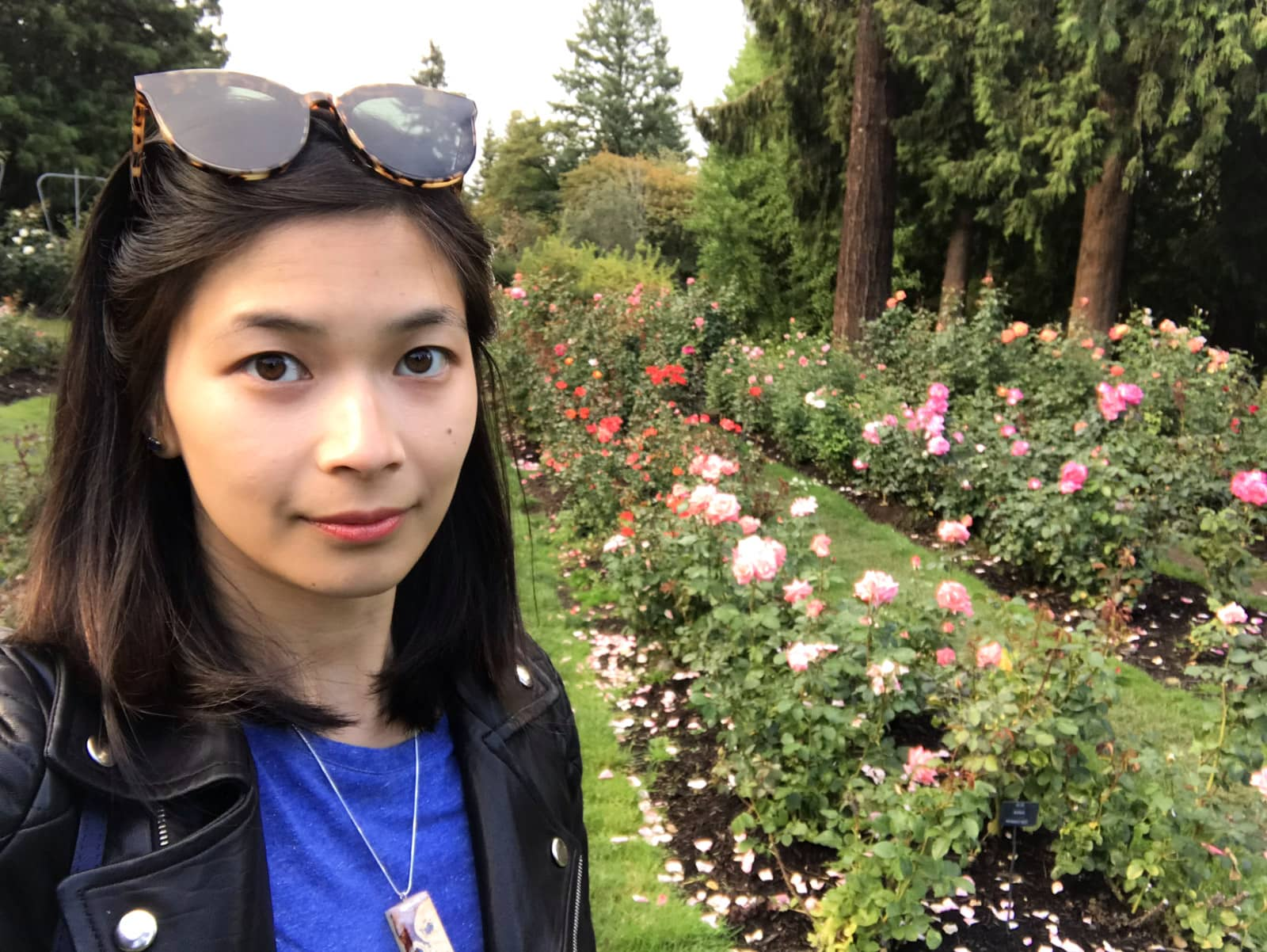 A selfie of a woman with short dark hair, wearing a blue shirt and black jacket. She is in the middle of a rose garden