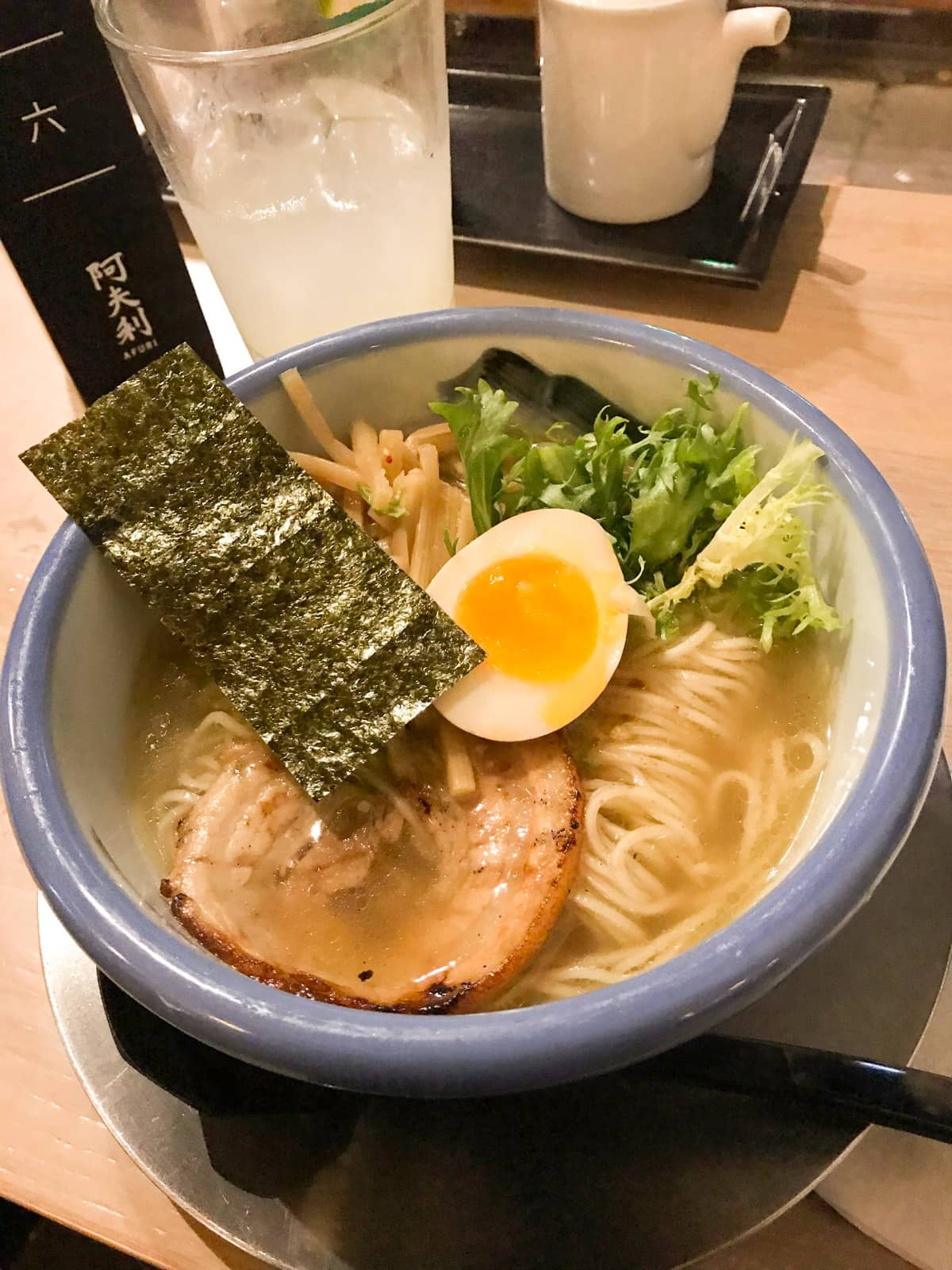 A blue-rimmed bowl filled with pork ramen. It is topped with half a boiled egg, bamboo shoots and nori seaweed