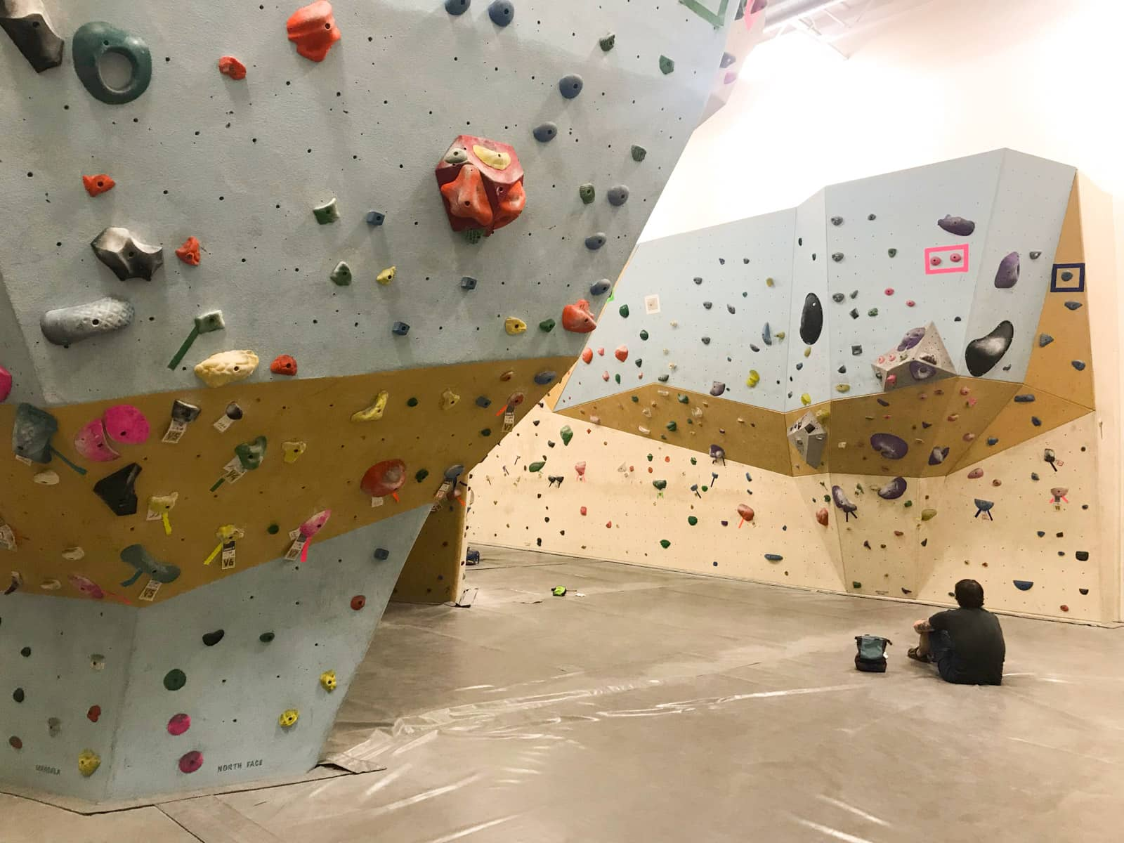 The inside of a bouldering/rock climbing gym. Coloured rock holds line the geometrically-shaped walls, and someone sits on the landing, facing away from the camera.