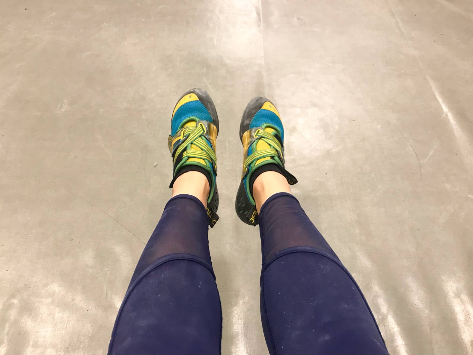 A top-down view of a woman's feet; she is wearing bright yellow and blue rock climbing shoes, and navy blue leggings.