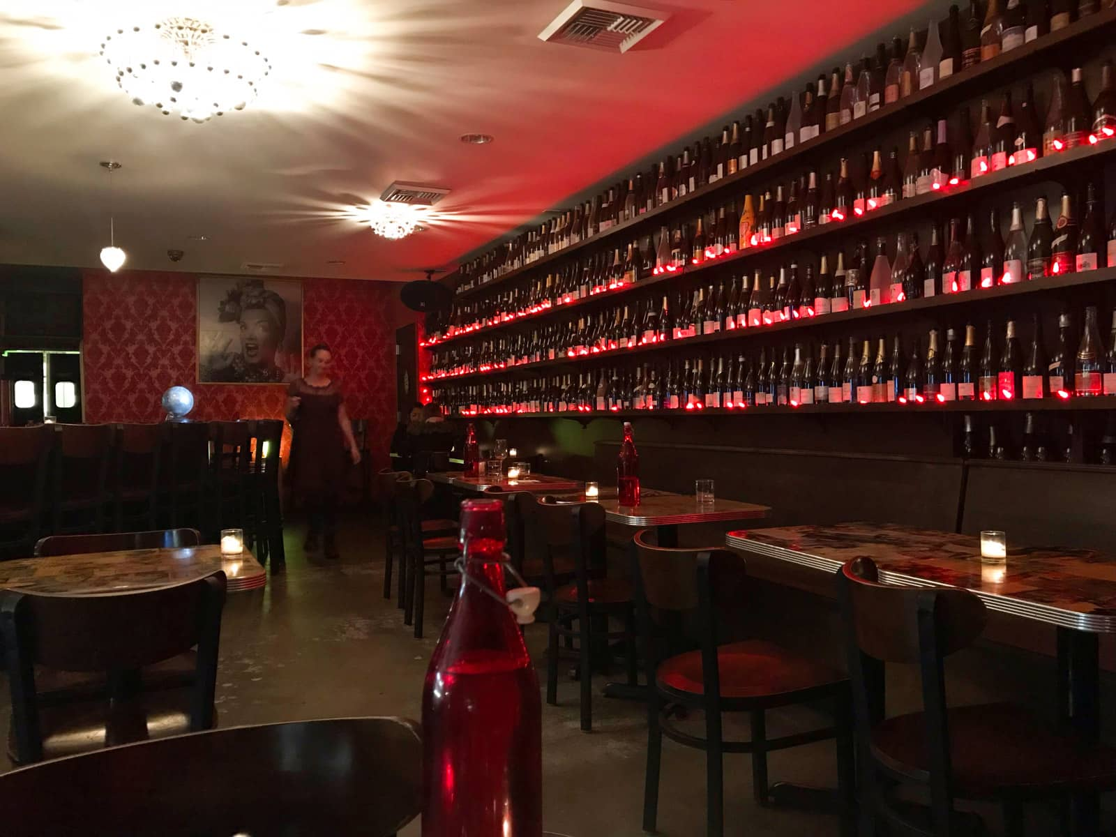 The dark and dimly lit interior of a cafe, with red decor. Wine bottles line the walls along with fake red candles.