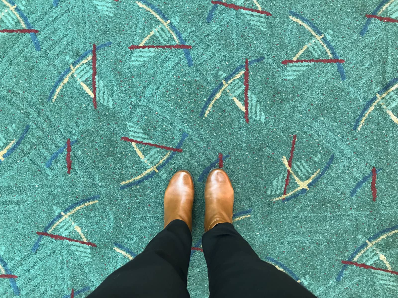 A top-down view of a woman with brown boots on her feet. She is standing on a teal green carpet with a repeating pattern