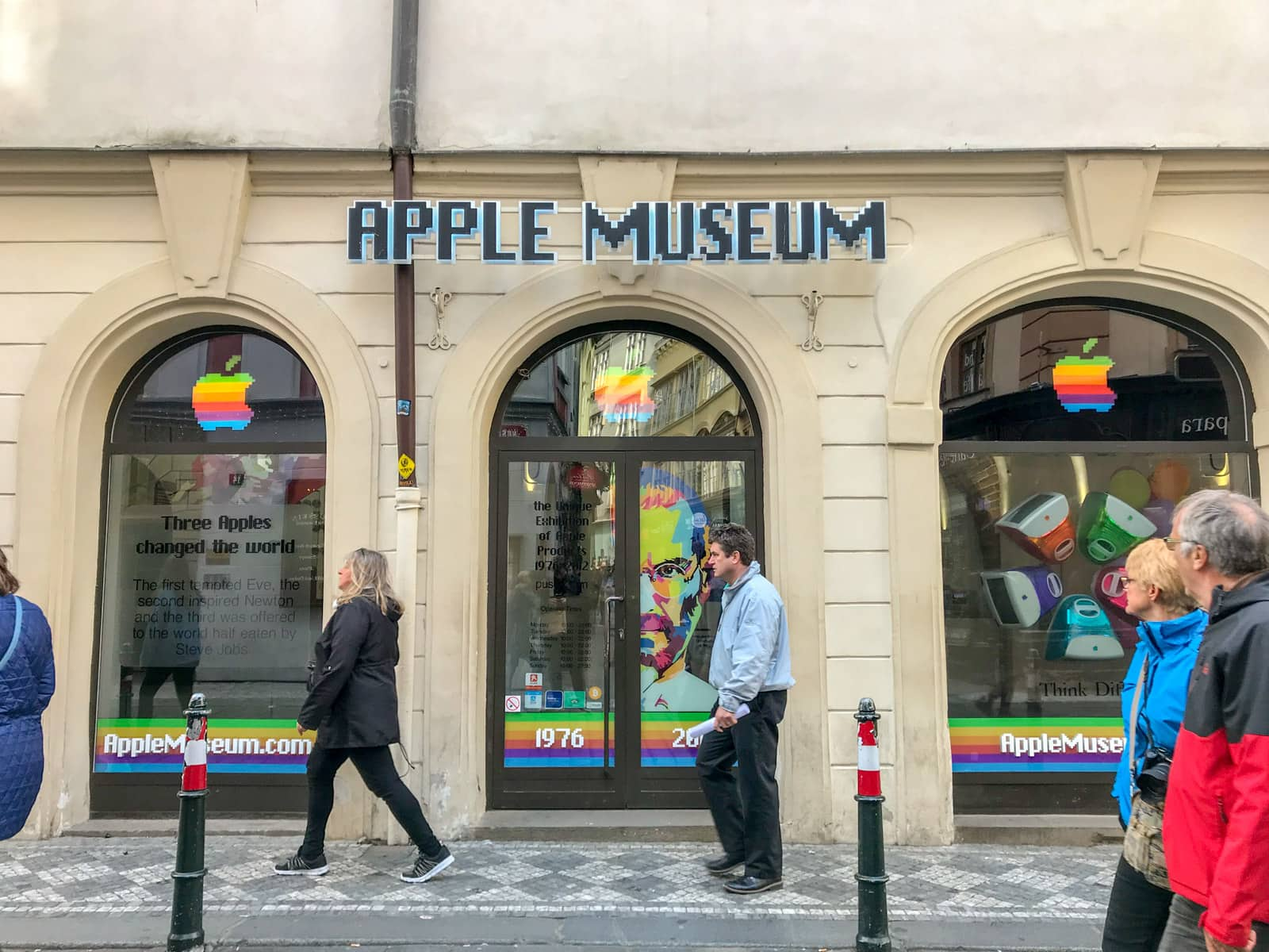 "Three arched windows, above which reads a sign ""Apple museum"". In the windows is rainbow-coloured signage and the Apple logo"