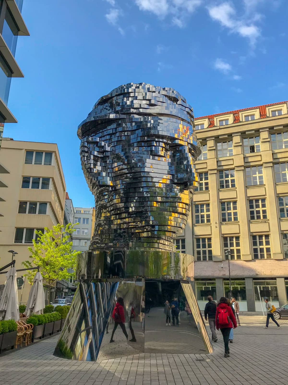 A statue of a person's head, with a reflective, silver surface, cut horizontally into slices, some of which are partially rotated
