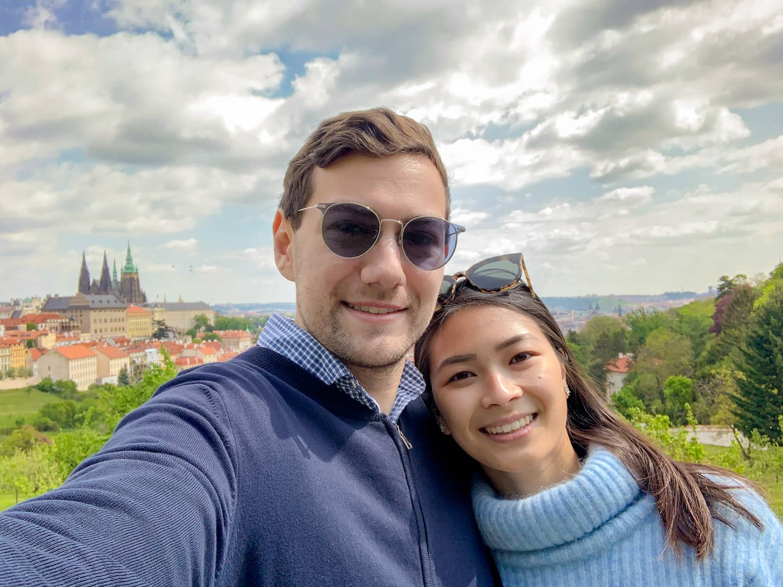A man and woman taking a selfie, with the city of Prague in the background. The man has sunglasses on, and is wearing a dark jacket, the woman has sunglasses on top of her head and is wearing a light blue sweater.