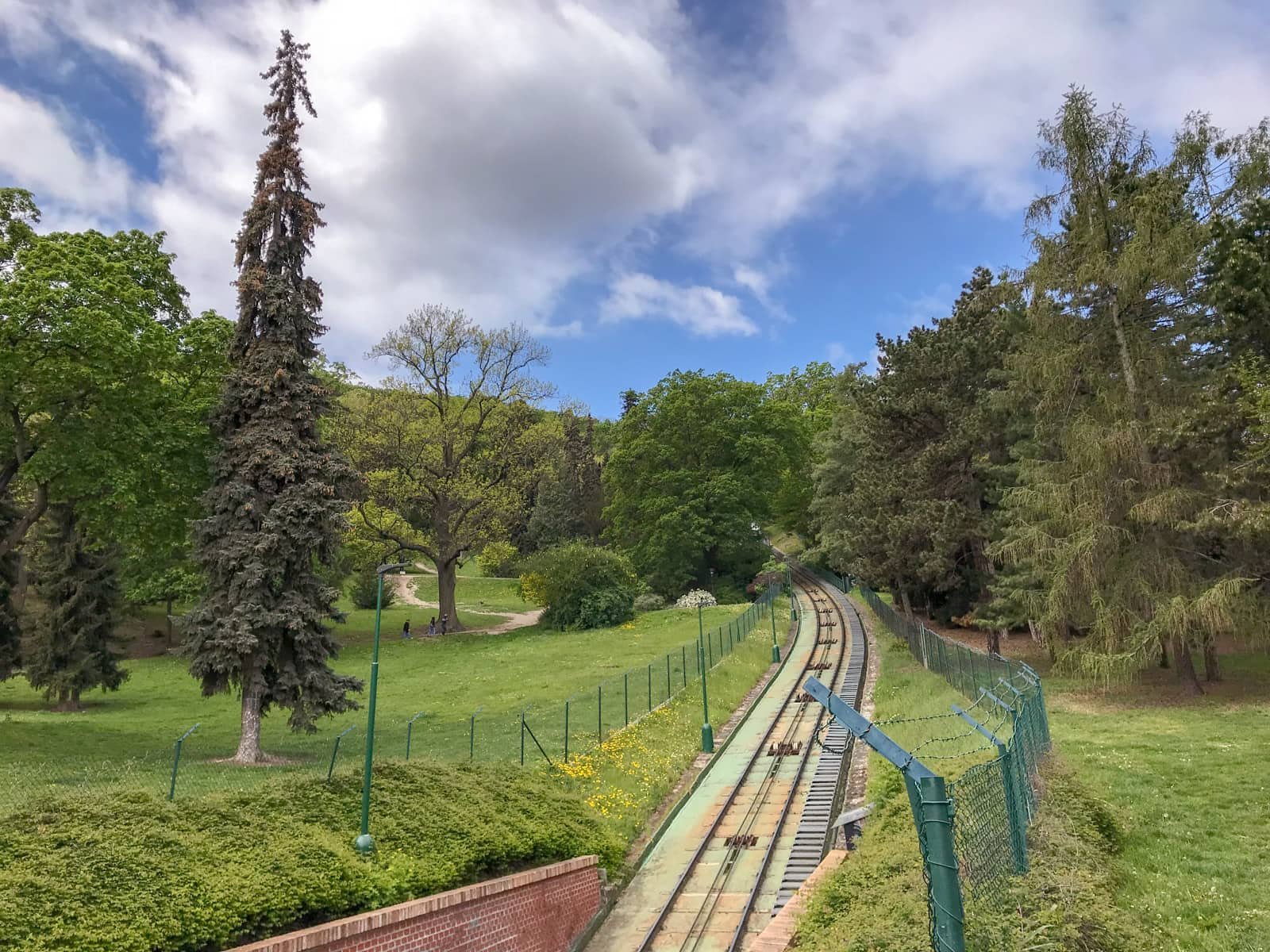 A railway going uphill through some trees. The tracks are fenced off by green wire fencing.