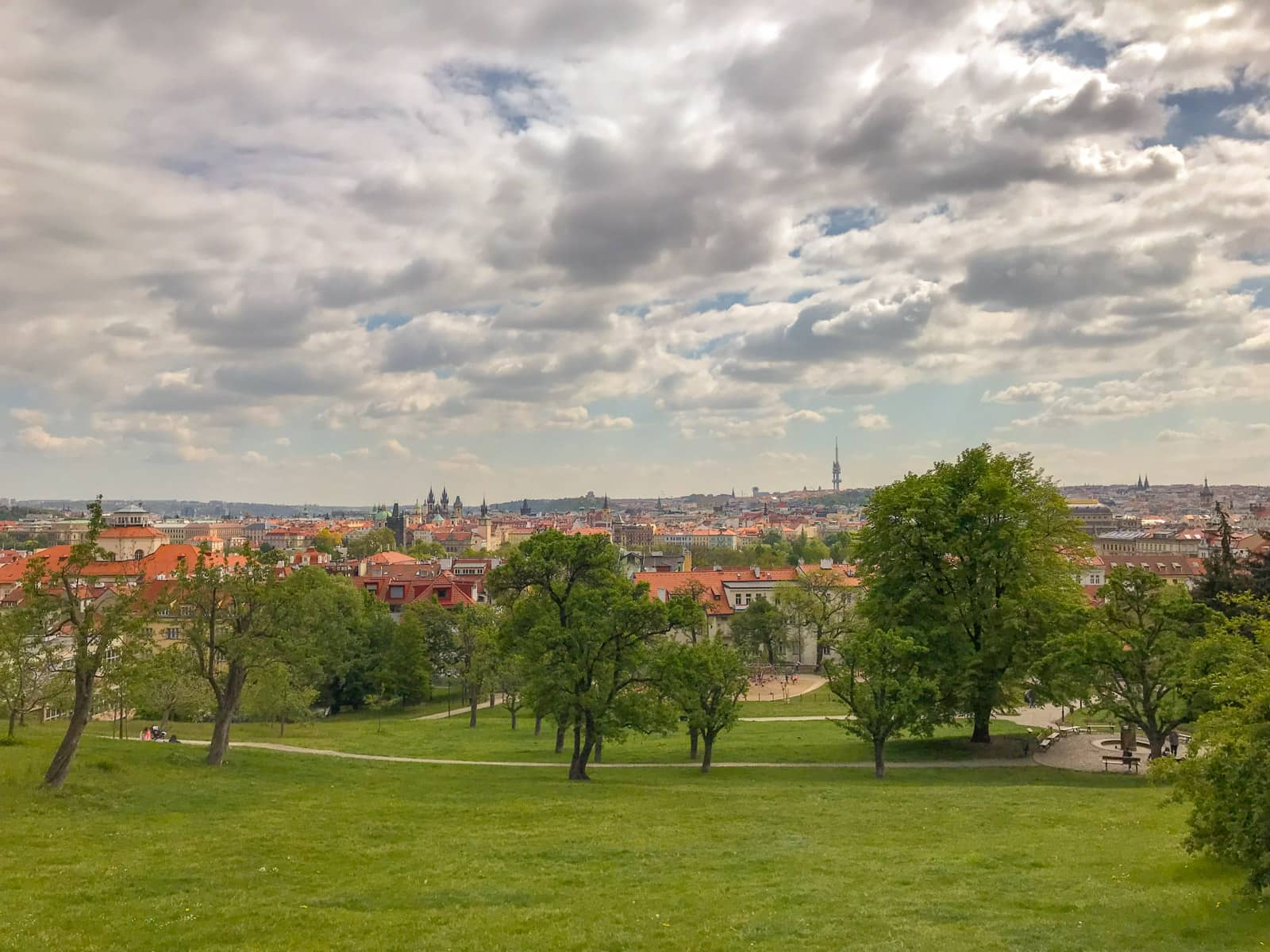 A view of Prague with a wide area of green in the foreground. There are many clouds I the sky