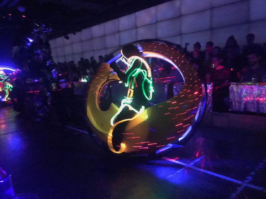 In a dark room with an open area, a person sits on a bike that is the shape of a large circular wheel. The person is in a dark costume with glowing wires woven throughout it. Shadows of an audience can be seen in the background.