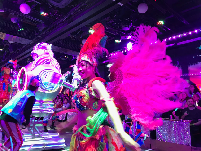 A girl dressed up in a costume consisting of a crop top and skirt, with big feather wings attached to her back. Purple lighting from the ceiling of the room colours her face and wings. In the background is a tall metallic robot.