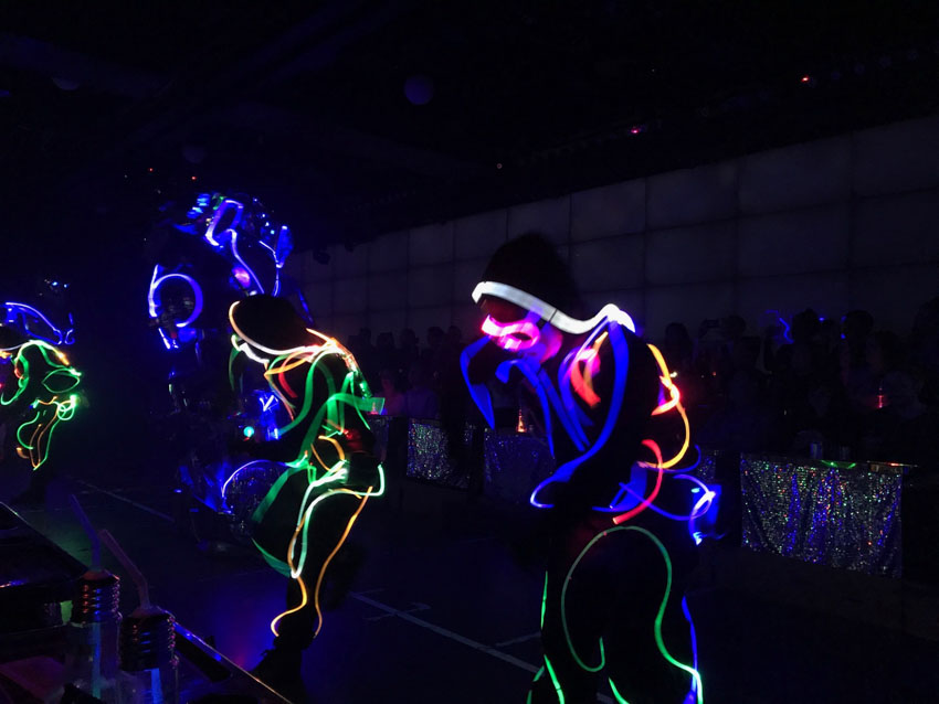 A dark room with several people in it, mid-dance, wearing black costumes with glowing wires woven through.