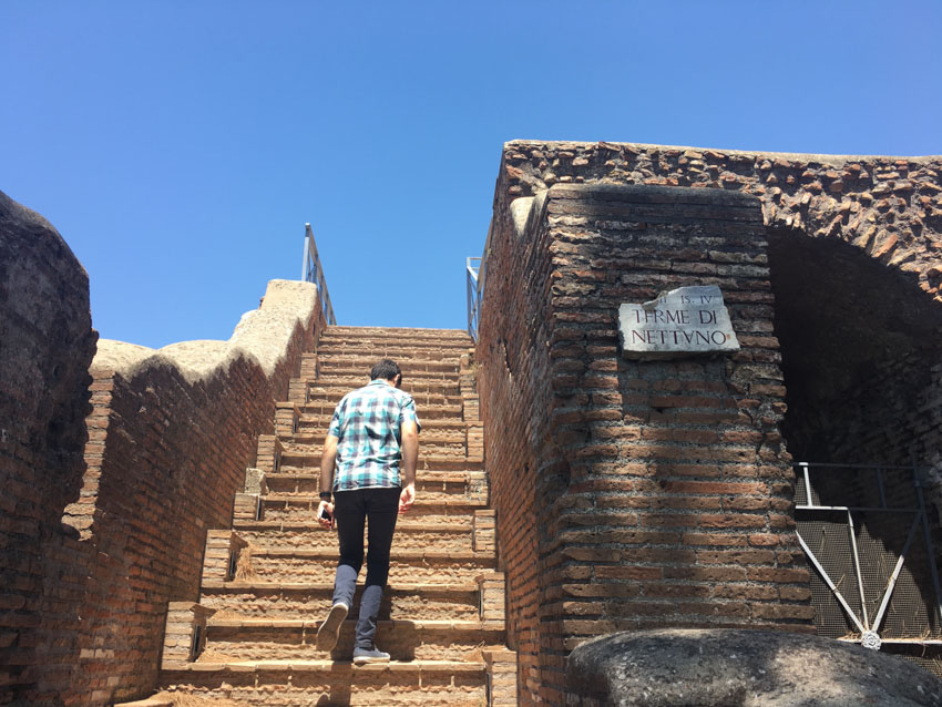 Nick walking up some stairs in a ruin in Ostia Antica