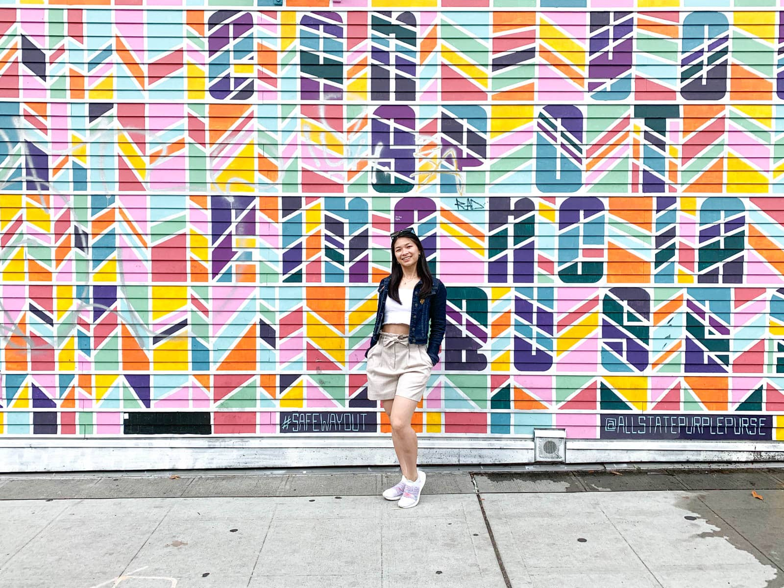 A woman with short dark hair, wearing a light coloured top and shorts, white shoes, and a denim jacket, standing in front of a colourful mural with her hands in her pockets.