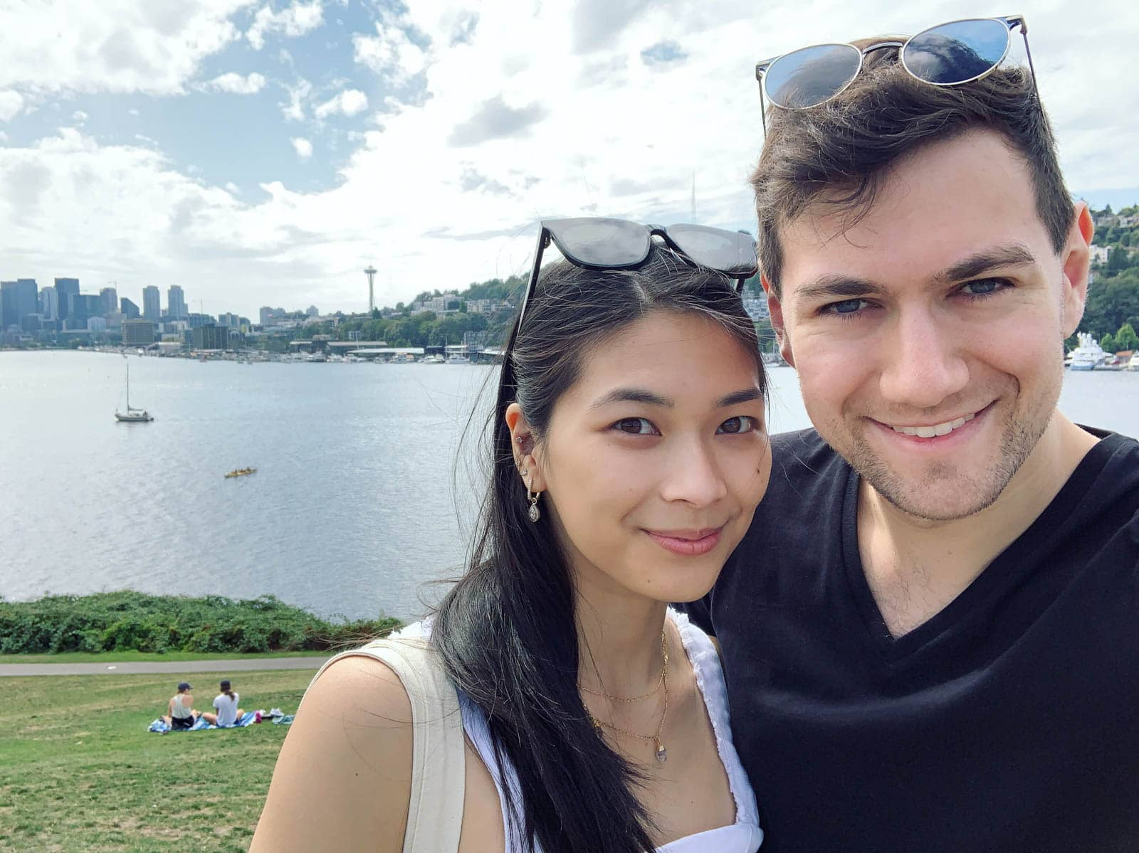 A selfie of a man and woman, with a large lake and a city skyline in the background. There is a couple sitting on the grass behind them. The man and woman have sunglasses on top of their heads and are smiling.